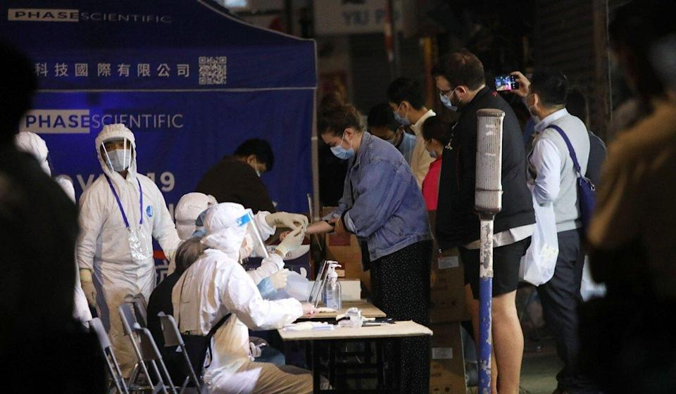Residents under lockdown in Yau Ma Tei queue to get tested for Covid-19 on Tuesday. Photo: K.Y. Cheng