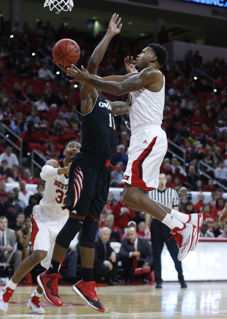 North Carolina State's Trevor Lacey (1) drives to the basket as Cincinnati's Gary Clark (11) defends during the first half of an NCAA college basketball game Tuesday, Dec. 30, 2014, in Raleigh, N.C. (AP Photo/The News & Observer, Ethan Hyman)