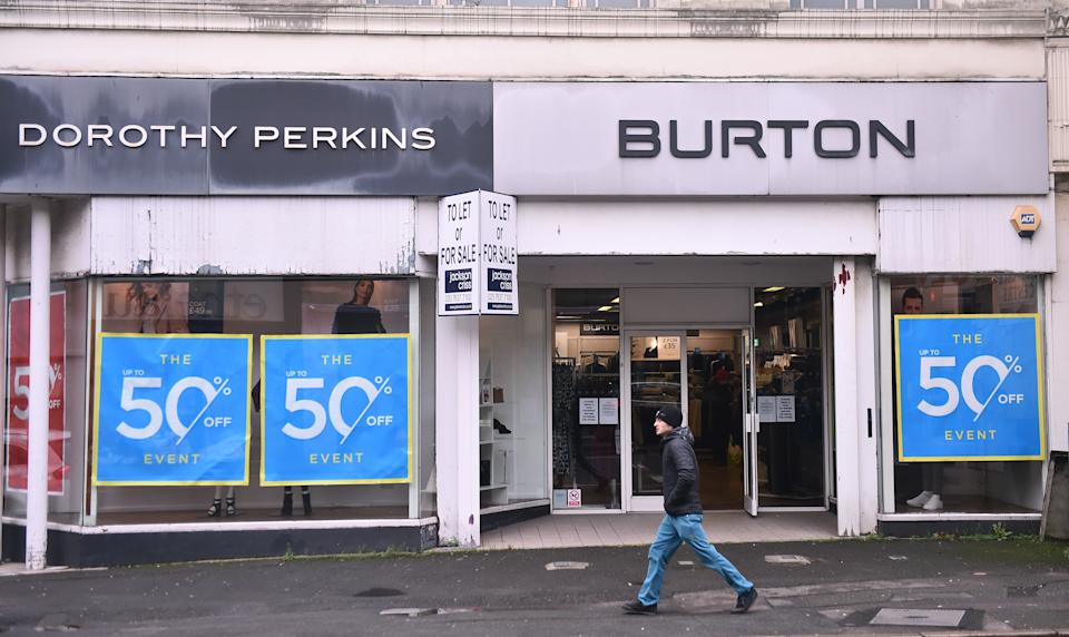 STOKE-ON-TRENT, ENGLAND - DECEMBER 07: A man walks past a Dorothy Perkins and Burtons store on December 07, 2020 in Stoke-on-Trent, Staffordshire, England.  Sir Philip Green's retail empire, Arcadia is facing collapse, putting 13,000 jobs at risk.  (Photo by Nathan Stirk/Getty Images)