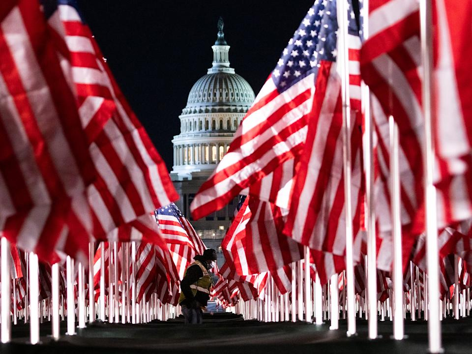 <p>A person walks through the public art display 'Field of Flags', made up of over 200,000 flags intended to represent the American people who are unable to attend the upcoming presidential inauguration</p> (EPA)