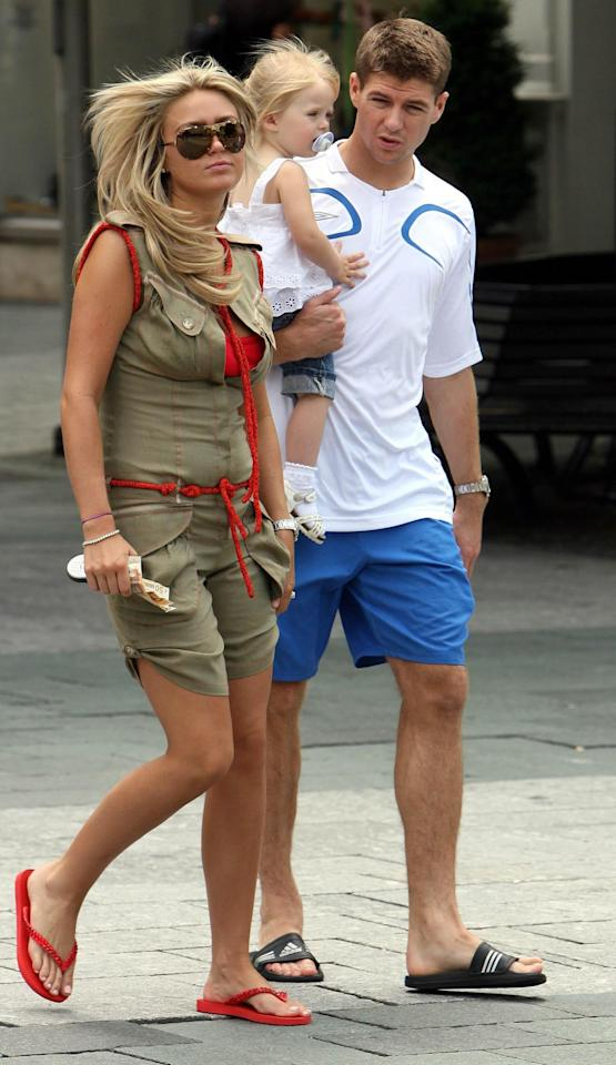 <p>Remember Alex Curran? Steven Gerrard's then-girlfriend – the couple tied the knot in 2007 – was a firm member of the original WAG clan. Here, the couple are pictured with their first daughter, Lilly-Ella, during the 2006 World Cup quarter finals in Germany. <em>[Photo: Getty]</em> </p>