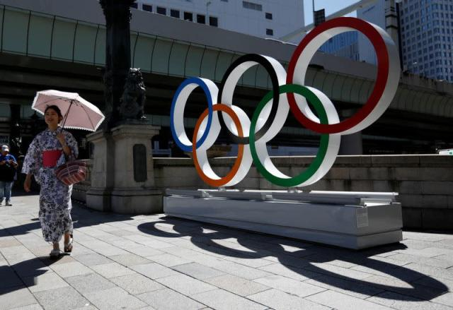 FILE PHOTO: A woman wearing the yukata, or casual summer kimono, walks past Olympic rings displayed at Nihonbashi district in Tokyo