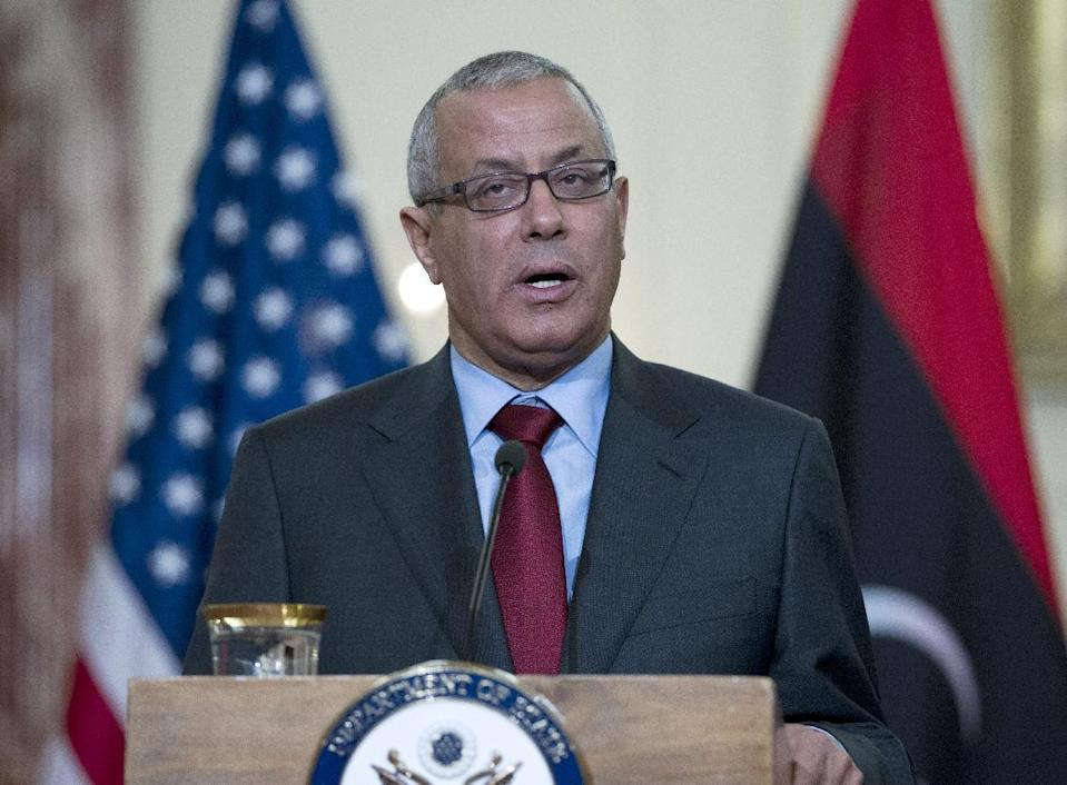 """FILE - In this March 13, 2013 file photo, Libyan Prime Minister Ali Zidan speaks during a joint news conference with U.S. Secretary of State John Kerry at the State Department in Washington. Over the past three days, militiamen stormed the headquarters of the Interior Ministry and state-run TV and besieged the Foreign Ministry while publicly calling for the removal of Gadhafi-era officials from government posts and the passage of the so-called """"isolation law,"""" which would bar from political life anyone who held any position —even minor— under the ousted autocrat's regime. However, analysts and democracy advocates believe militiamen are using the isolation law as a way to get rid of Zidan, who has vowed to restore the authority of the state and disband the armed groups that have become a power unto themselves in Libya. Many of the militias have an Islamist ideology, while Zidan is seen as more secular and liberal.. (AP Photo/Jose Luis Magana, File)"""
