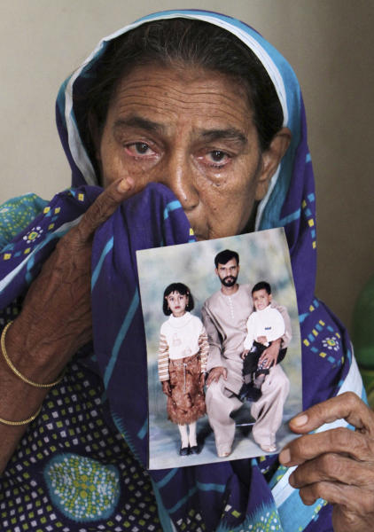 In this Friday, Oct. 19, 2012 photo, Pakistani Aisha Bano, 75, cries while holding a portrait of her son Muhammad Javed and his family, who was killed in a fire at a garment factory last September, at the family's house in Karachi, Pakistan. At the only morgue in Pakistan's largest city lie the blackened remains of 32 people killed in one of the worst industrial accidents in the country's history, wrapped in white plastic body bags waiting for DNA tests to determine who they are and where they belong. (AP Photo/Fareed Khan)
