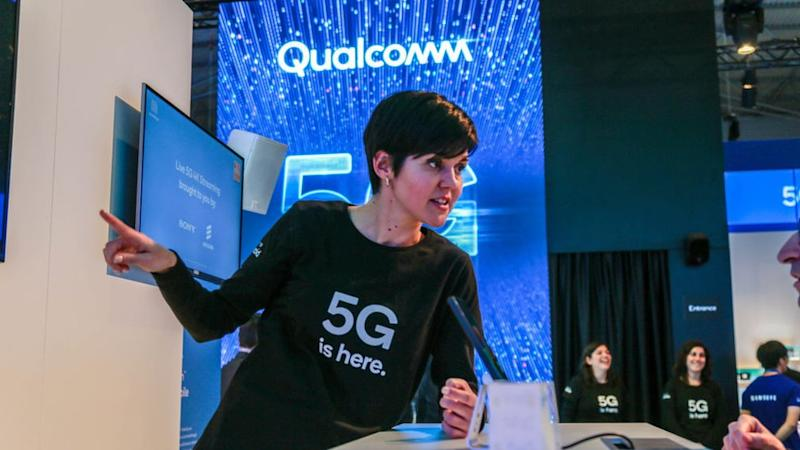 An employee talks about 5G at Qualcomm's booth at Mobile World Congress 2019 in Barcelona