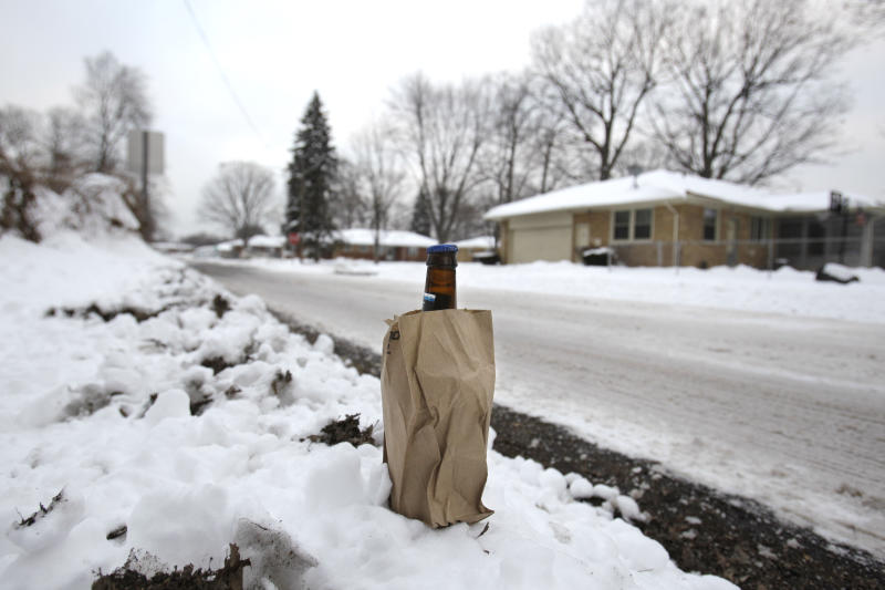 This Wednesday, Feb. 23, 2011 picture shows a previously opened bottle of beer resting in the snow on the side of the road in the Detroit suburb of Southfield, Mich. Many in the black middle class moved out of Detroit and settled in the northern suburbs years ago; now, due to foreclosures, it is easy to buy or rent houses on the cheap here. The result has been a new, poorer wave of arrivals from the city, and growing tensions between residents and the newcomers. (AP Photo/Carlos Osorio)