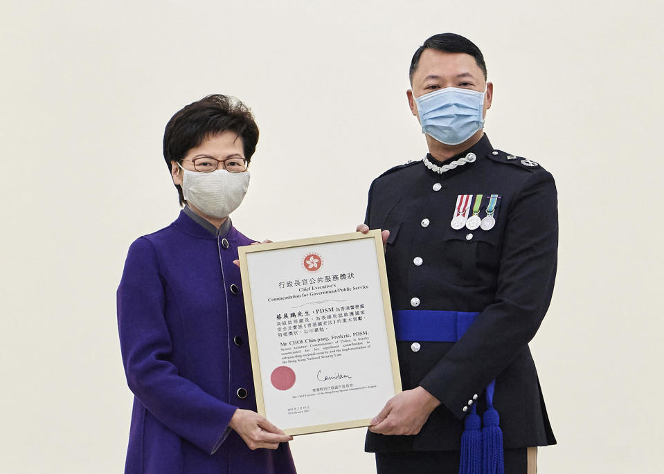 In this photo released by Hong Kong Government Information Services, Hong Kong Chief Executive Carrie Lam, left, presents the award to Hong Kong's Director of National Security Frederic Choi at Government House in recognition of his significant contributions to safeguarding national security in Hong Kong on Feb. 10, 2021. The top Hong Kong national security officer was reportedly caught up in a raid on an unlicensed massage business, and will face a police force investigation into the alleged misconduct. Choi has since been put on leave after the incident, according to Hong Kong police chief Chris Tang. (Hong Kong Government Information Services via AP)