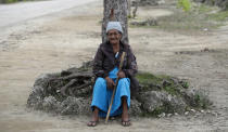 In this April 7, 2019, photo, a local woman sits under a tree in Nuku'alofa, Tonga. China is pouring billions of dollars in aid and low-interest loans into the South Pacific, and even in the far-flung kingdom of Tonga there are signs that a battle for power and influence among much larger nations is heating up and could exact a toll. (AP Photo/Mark Baker)