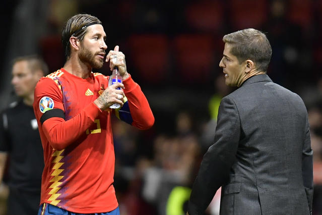 Spain's coach Roberto Moreno, right, speaks with Sergio Ramos during the Euro 2020 group F qualifying soccer match between Spain and Faroe Islands at the Molinon, stadium in Gijon, Spain, Sunday, Sept. 8, 2019. (AP Photo/Alvaro Barrientos)