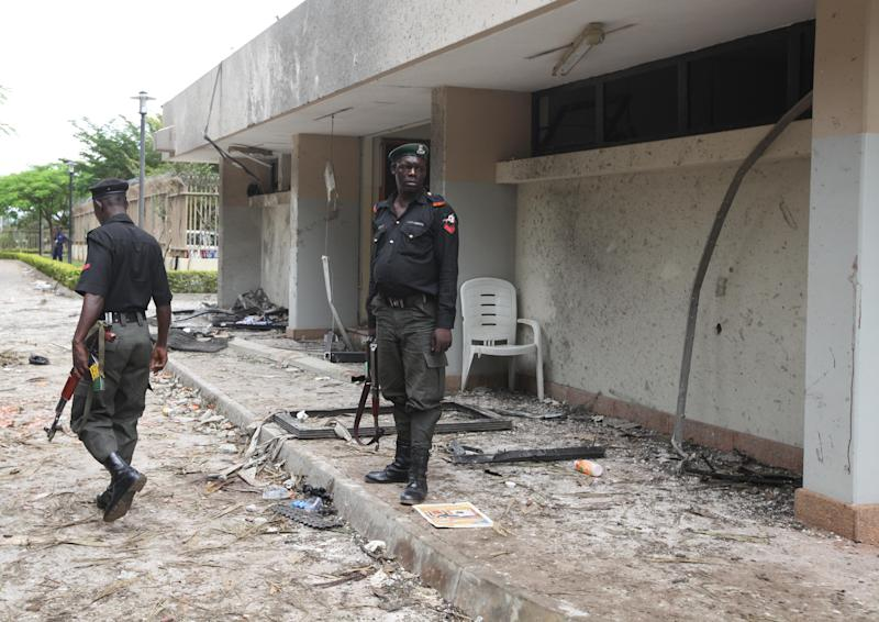 "Nigeria police guard at the bombed site of  the United Nation's office Sunday, Aug. 28, 2011 after a car bombing  on Friday in Abuja, Nigeria which killed at least 19 people. Nigeria's president says his government will bring terrorism ""under control"". (AP Photo/Sunday Alamba)"