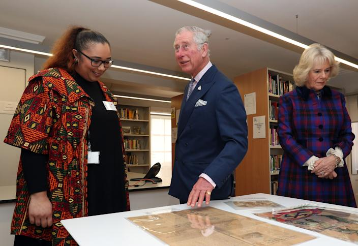 LONDON, ENGLAND - FEBRUARY 16: Prince Charles, The Prince of Wales and the Camilla, Duchess of Cornwall are shown items of historical significance by Natalie Fiawoo (left) during their visit to the Black Cultural Archives in Brixton on February 16, 2017 in London, England.  (Photo by Jonathan Brady / WPA Pool - Getty Images)