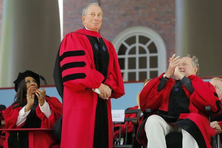 Former New York Mayor Michael Bloomberg stands to receive an honorary Doctor of Laws degree as fellow honorary degree recipients musician Aretha Franklin (L) and former United States President George H.W. Bush (R) applaud during the 363rd Commencement Exercises at Harvard University in Cambridge, Massachusetts May 29, 2014. REUTERS/Brian Snyder