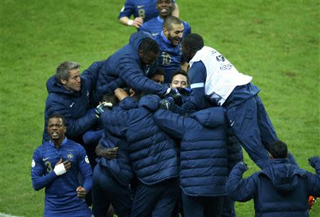 France's soccer team players celebrate after Ukraine's Oleg Guslev (unseen) scored an own goal during their 2014 World Cup qualifying second leg playoff soccer match against Ukraine at the Stade de France in Saint-Denis near Paris