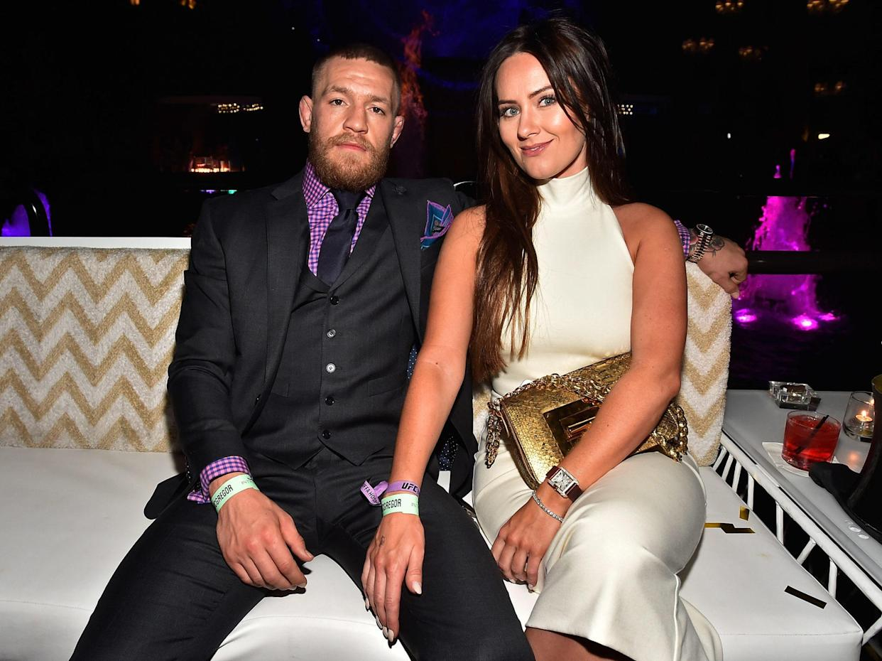 Conor McGregor sits with his wife.