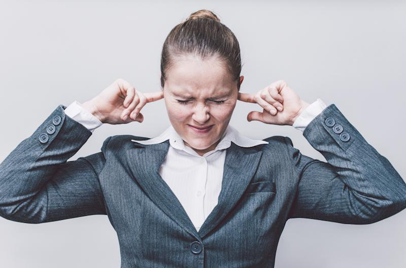 Businesswoman putting finger in ears.