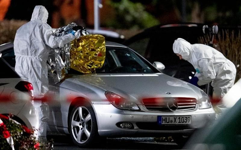 Police forensics officers search a Mercedes at one of the crime scenes - Michael Probst /AP