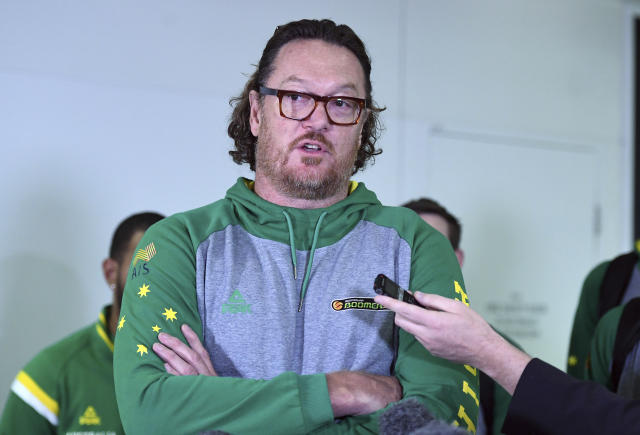 In this July 4, 2018, photo, Australia assistant coach and former NBA star Luc Longley speaks to the media as he arrives at Brisbane airport, after the violence that marred a World Cup qualifying match between the teams on Monday. Longley describes the bench-clearing brawl which saw 13 players, including four Australians, ejected from the match as the worst thing he had seen on a basketball court. (Dan Peled/AAP Image via AP)