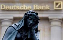 FILE PHOTO: A statue is seen next to the logo of Germany's Deutsche Bank in Frankfurt