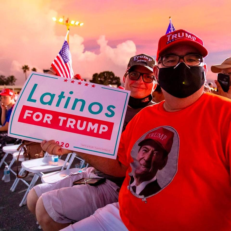 Trump supporters and Miami residents Juan Llanes, 57, and George Hubbard, 53, sit as they wait for Donald Trump Jr. to speak at the 'Fighters against Socialism' event at the Wings Over Miami Museum in Miami, Florida, on Sunday, October 11, 2020.
