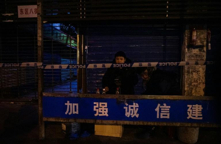 Security personnel stood guard outside the closed Huanan Seafood Wholesale Market, where officials said a man who died from a respiratory illness had purchased goods