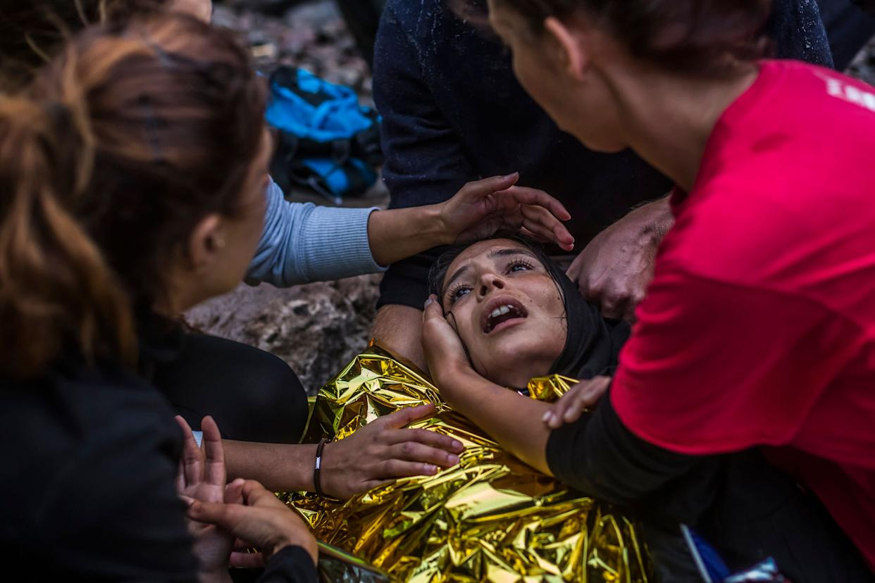 A woman reacts as she arrived with other refugees on the shores of the Greek island of Lesbos after crossing the Aegean sea from Turkey on a inflatable boat on October 1, 2015 near village of Skala Sikaminias, Greece.