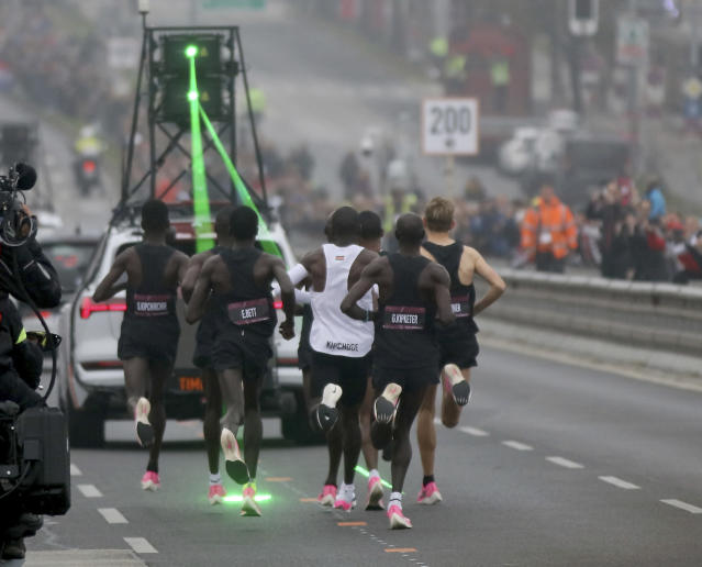 Marathon runner Eliud Kipchoge from Kenya, white vest, and his first pacemaking team run on the Reichsbrucke during the INEOS 1:59 Challenge attempt to run a sub two-hour marathon in Vienna, Austria, Saturday, Oct. 12, 2019. (AP Photo/Ronald Zak)
