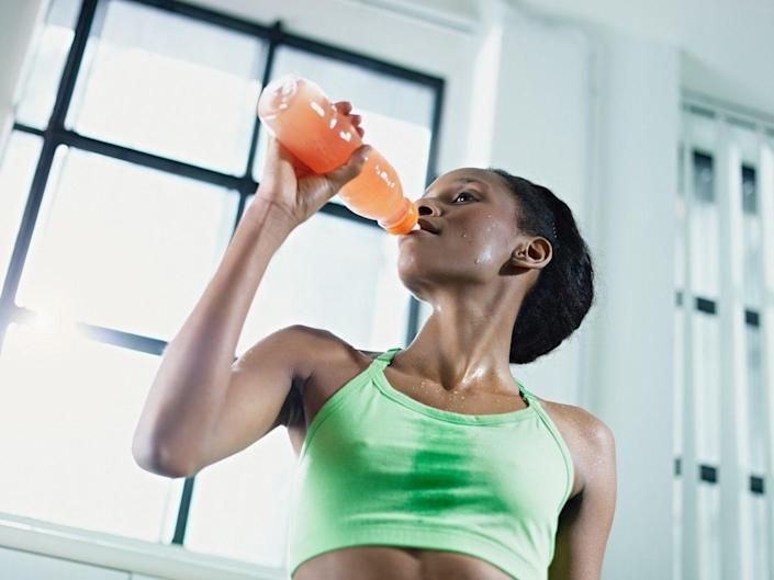 african american woman in sportswear with energy drink in gym