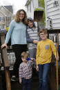 Stephanie Owens and her three children Lucas, 12: Reid, 8; and Cole, 3. Tend to a small garden at their home Wednesday March 25 , 2020, in Glen Allen, Va. Owens is a pharmacist who has had to continue to go to work, but has been able to spend more time with her kids because they are home from school . One of the activities that they have done is planting the garden. (AP Photo/Steve Helber)