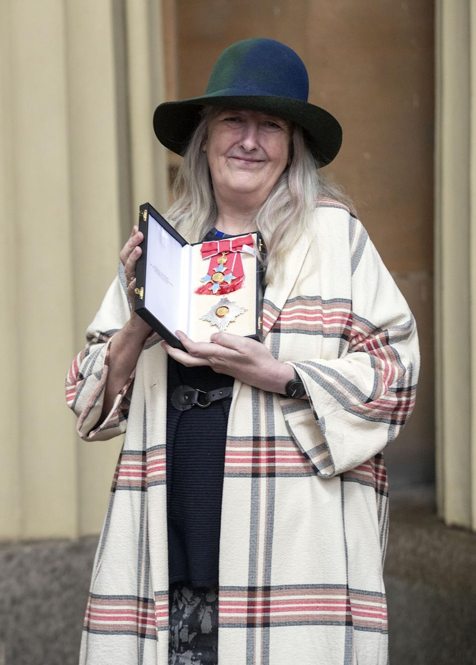 Mary Beard poses with her medal and insignia after she was appointed a Dame Commander of the Order of the British Empire (DBE) at an investiture ceremony at Buckingham Palace in London on December 7, 2018. (Photo by STEVE PARSONS / POOL / AFP via Getty Images)