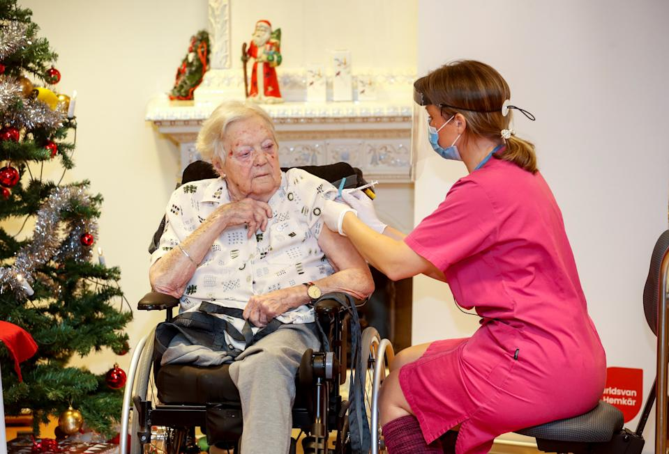 Nurse Ann-Louise Broberg injects the coronavirus disease (COVID-19) vaccine to nursing home resident Gun-Britt Johnsson, the first person to receive it in the country, in Mjolby, Sweden, December 27, 2020. Stefan Jerrevang/TT News Agency/via REUTERS      ATTENTION EDITORS - THIS IMAGE WAS PROVIDED BY A THIRD PARTY. SWEDEN OUT. NO COMMERCIAL OR EDITORIAL SALES IN SWEDEN.