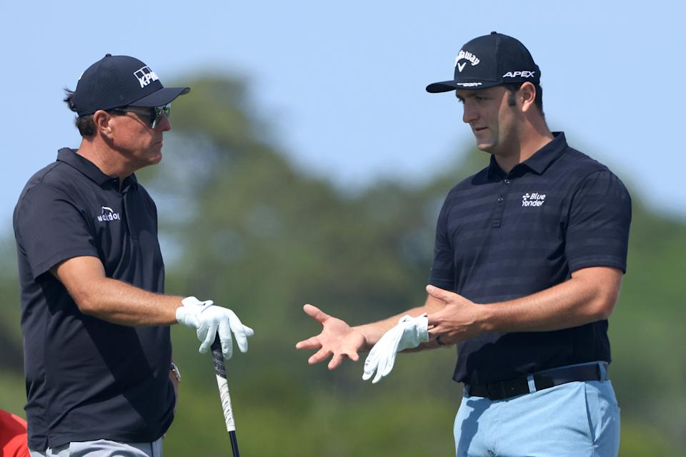 Phil Mickelson (pictured left) talks with Jon Rahm (pictured right) during a practice round.