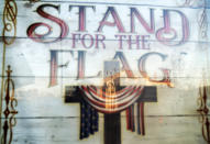 """A mural of the Virgin Mary, painted on the side of a building, is reflected in a poster which reads """"Stand for the Flag, Kneel for the Cross,"""" outside a church in Roseville, Mich., Saturday, Oct. 31, 2020. As the traditional Election Day closes in, Americans are exhausted from constant crises, on edge because of volatile political divisions and anxious about what will happen next. (AP Photo/David Goldman)"""