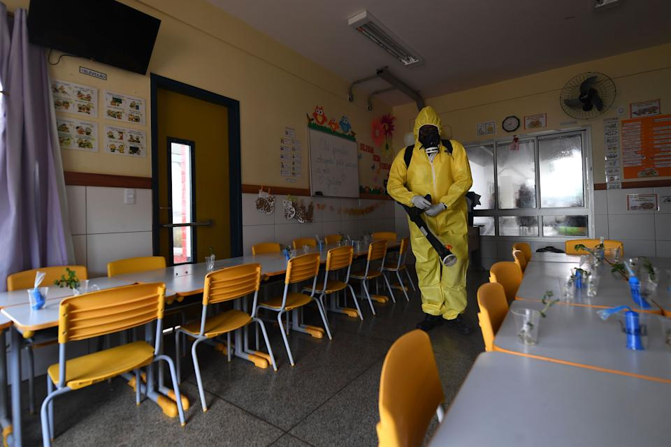 A Federal District's employee disinfects a public school as a measure against the spread of the new coronavirus in Brasilia, on August 5, 2020. - The local government has begun preparations for the safe reopening of schools in early September, as restrictions related to the COVID-19 lockdown are eased. (Photo by EVARISTO SA / AFP) (Photo by EVARISTO SA/AFP via Getty Images)
