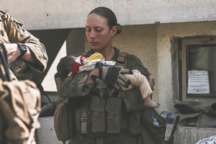 In this Aug. 20, 2021, image provided by the U.S. Marine Corps, Marines assigned to the 24th Marine Expeditionary Unit (MEU), including Sgt. Nicole Gee calms an infant during an evacuation at Hamid Karzai International Airport in Kabul, Afghanistan. Officials said Aug. 28, that Gee of Sacramento, Calif., was one of the Marines killed in Thursday's bombing at the airport. (Sgt. Isaiah Campbell/U.S. Marine Corps via AP)
