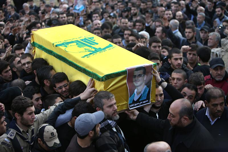 Mourners carry the coffin of Ali Khadra, who was killed Thursday by a bomb explosion, during his funeral procession in the southern suburb of Beirut, Lebanon, Saturday, Jan. 4, 2014. An explosion tore through a crowded commercial street Thursday in a south Beirut neighborhood that is bastion of support for the Shiite group Hezbollah, killing several people, setting cars ablaze and sending a column of black smoke above the Beirut skyline. (AP Photo/Hussein Malla)