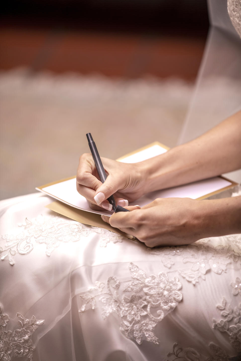 Wedding ceremony vows being written by a bride to be on a pad of paper