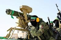 Members of the Ezz-Al Din Al-Qassam Brigades, the armed wing of the Palestinian Hamas movement, parade with an anti-tank weapon in Rafah in the southern Gaza Strip on May 28