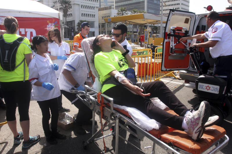 Paramedics treat a marathon runner suffering from heat In Tel Aviv, Israel, Friday, March 15, 2013. An Israeli soldier died of a heat stroke Friday after completing a half-marathon race in Tel Aviv, prompting Israel's minister of public security to criticize organizers for allowing the race to take place during a heat wave. (AP Photo/Roni Schutzer)   ISRAEL OUT