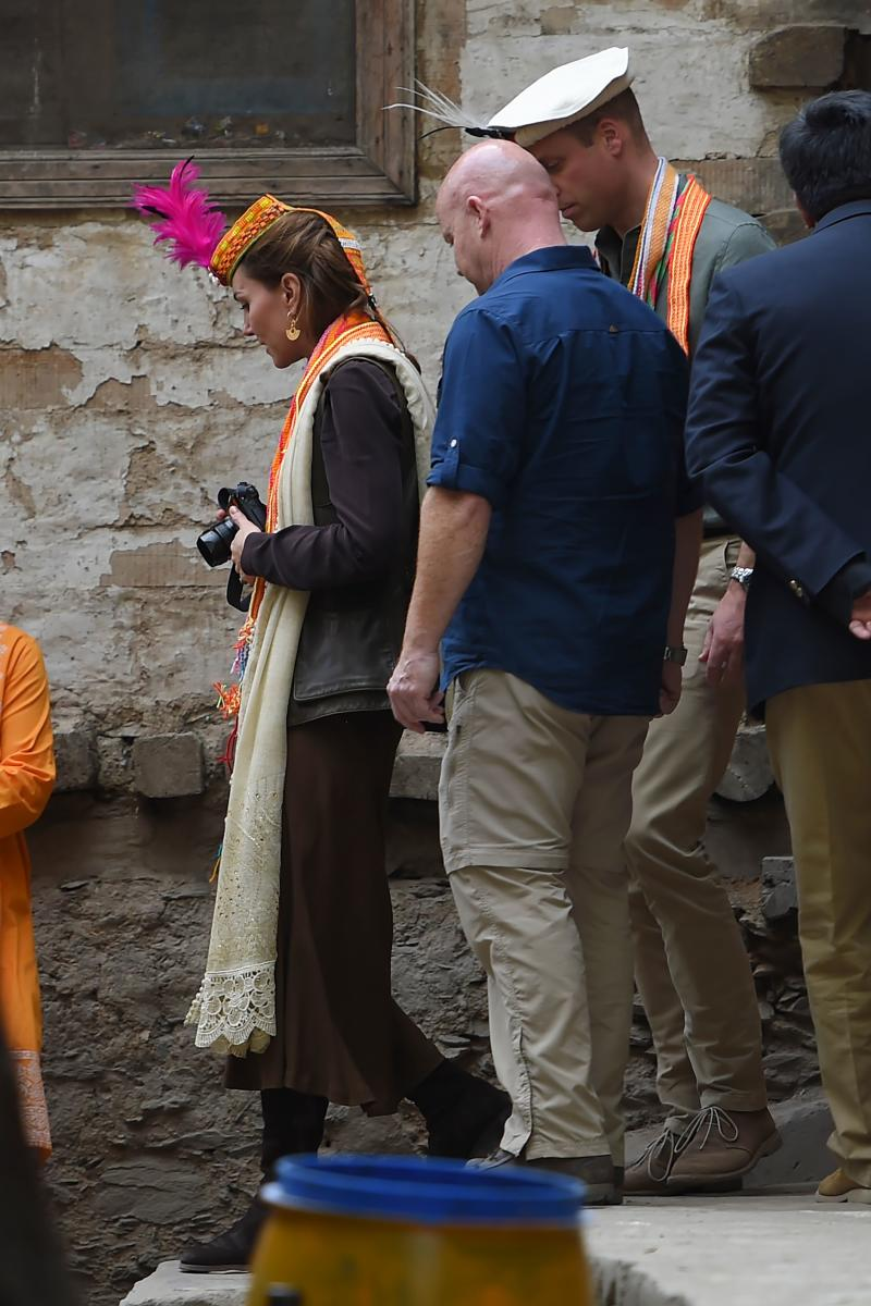 Britain's Prince William (C), Duke of Cambridge follows his wife Britain's Catherine (L), Duchess of Cambridge, as she holds a camera during their visits at the Kalash tribe village in Bumburate Valley in Pakistan northern Chitral District on October 16, 2019. - Prince William and his wife Kate flew near the Afghan border to visit a remote Hindu Kush glacier on October 16, after a morning spent trying on feathered traditional caps and luxurious shawls in Pakistan's mountainous north. (Photo by FAROOQ NAEEM / AFP) (Photo by FAROOQ NAEEM/AFP via Getty Images)
