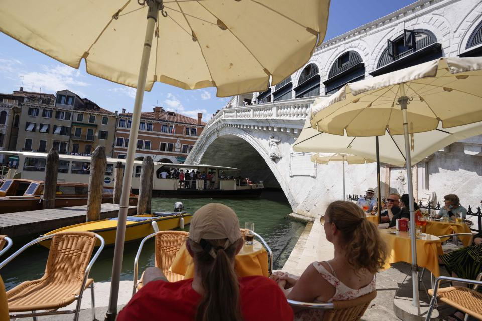 Customers sit at a cafe, in Venice, Italy, Thursday, June 17, 2021. After a 15-month pause in mass international travel, Venetians are contemplating how to welcome visitors back to the picture-postcard canals and Byzantine backdrops without suffering the indignities of crowds clogging its narrow alleyways, day-trippers perched on stoops to imbibe a panino and hordes of selfie-takers straining for a spot on the Rialto Bridge or in front of St. Mark's Basilica. (AP Photo/Luca Bruno)