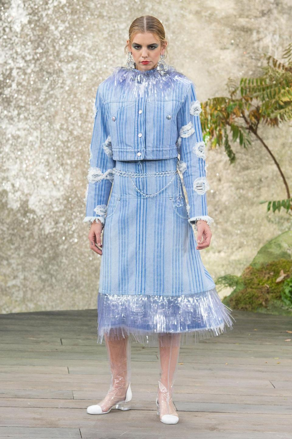 <p>A light wash striped jacket and skirt with PVC fringe and floral appliqués was a standout at the SS18 Chanel show. (Photo: ImaxTree) </p>