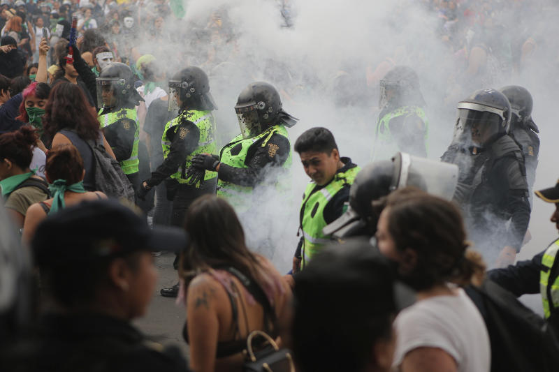 A cloud of smoke engulfs police after they put out a fire started by protesters during a women's rights protest in Mexico City, Saturday Sept. 28, 2019. Mexican women on Saturday marched for abortion rights, highlighting increased efforts across Latin America to lift some of the world's most restrictive abortion laws. (AP Photo/Anthony Vazquez)
