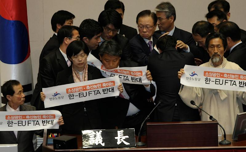 """National Assembly Speaker Park Hee-tae, top center, is surrounded by parliament officials as he attempts to sit his seat in a session to pass a bill to ratify the free trade agreement (FTA) with the European Union (EU) at the National Assembly in Seoul, South Korea, May 4, 2011. Labor Party lawmakers who tried to stop the passage held the banners reading """"Oppose free-trade agreement between the EU and South Korea."""" (AP Photo/Ahn Young-joon)"""