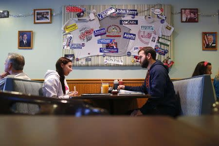 Chantal Roy (L) and Robert Desmarais sit down for breakfast under a collage of political campaign stickers at Chez Vachon in Manchester, New Hampshire December 17, 2014. REUTERS/Brian Snyder