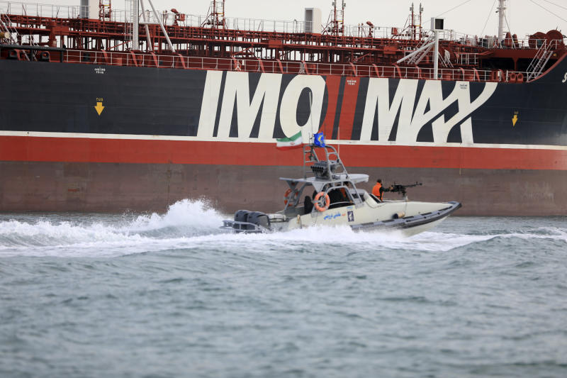 In this Sunday, July 21, 2019 photo, a speedboat of the Iran's Revolutionary Guard moves around a British-flagged oil tanker Stena Impero which was seized in the Strait of Hormuz on Friday by the Guard, in the Iranian port of Bandar Abbas. Global stock markets were subdued Monday while the price of oil climbed as tensions in the Persian Gulf escalated after Iran's seizure of a British oil tanker on Friday. (Morteza Akhoondi/Mehr News Agency via AP)