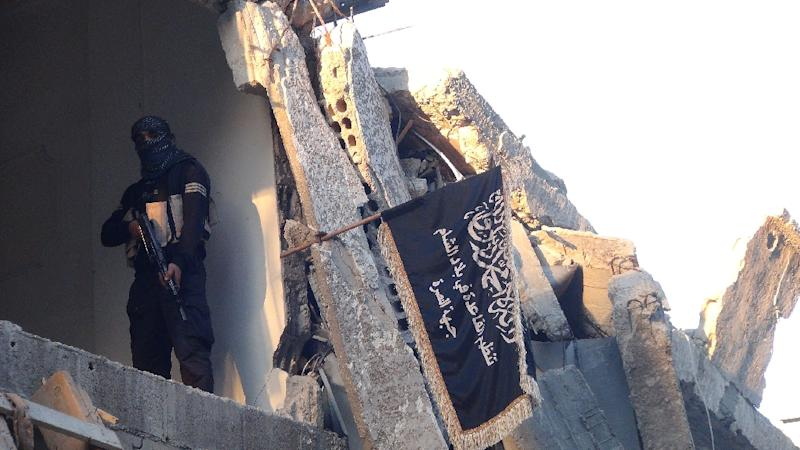 A fighter from al-Nusra Front poses next to the movement's flag in a destroyed building in Damascus on September 22, 2014