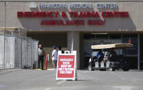 FILE - This June 10, 2020, file photo, shows the emergency room entrance at Valleywise Health Center hospital in Phoenix. Arizona is continuing to see slight downward trends with coronavirus hospitalizations as officials find more related deaths. (AP Photo/Ross D. Franklin, File)