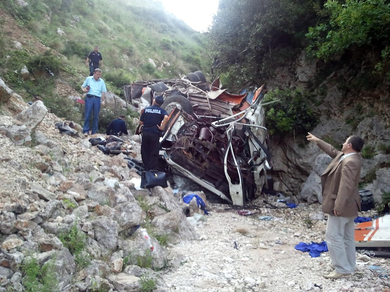 Rescue personnel attend the scene of a bus accident as the bus lies at the bottom of a cliff near Himare southern Albania on Monday, May 21, 2012. The accident killed a number of people and injured tens of others authorities said. Local prefect Edmond Velcani said the bus driver was among the people killed. The bus had been heading from the city of Elbasan to the southern city of Saranda. Police spokeswoman Klejda Plangarica said the bus fell some 80 meters (yards) off the road in Qafa e Vishes near the town of Himare, 137 miles (220 kilometers) south of the capital, Tirana, on Monday afternoon. (AP Photo)