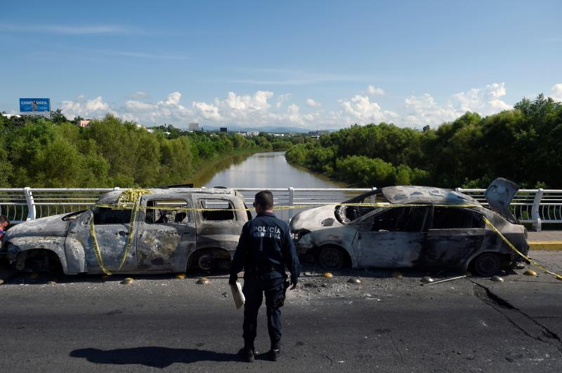 """A policeman stands next to burnt vehicles after heavily armed gunmen waged an all-out battle against Mexican security forces in Culiacan, Sinaloa state, Mexico, on October 18, 2019. - Mexico's president faced a firestorm of criticism Friday as his security forces confirmed they arrested kingpin Joaquin """"El Chapo"""" Guzman's son, then released him when his cartel responded with an all-out gun battle. (Photo by ALFREDO ESTRELLA / AFP) (Photo by ALFREDO ESTRELLA/AFP via Getty Images)"""