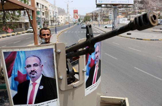 An STC fighter stands guard in Aden with a poster of STC chief Aidarous Zubaidi (NABIL HASAN/AFP/Getty Images)